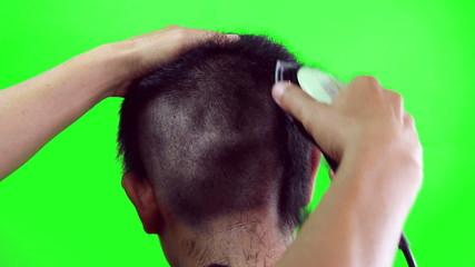 A boy having a haircut with hair clippers, green screen