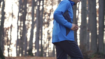 Young man jogging in autumn forest, super slow motion