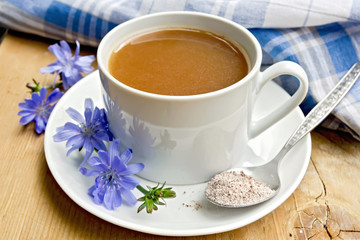 Chicory drink in white cup with flower and spoon on board