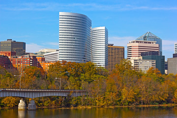 Modern building near Potomac River and trees with fall foliage.