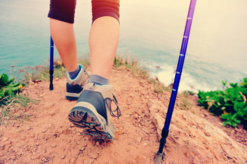 young fitness woman hiker legs on seaside mountain