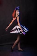 Teenage girl dancing on a black background
