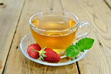 Tea with strawberries and mint on board