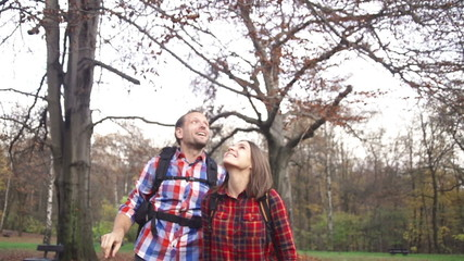 Happy hiker couple in autumn forest, super slow motion