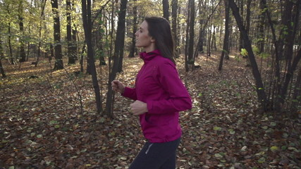 Pretty woman jogging in autumn forest