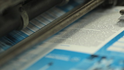Close-up of colorful printing of leaflets at printing house