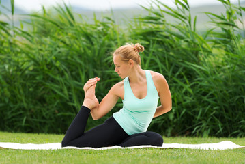 Woman making yoga one legged king pigeon pose