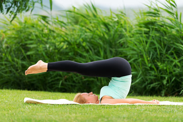Young woman doing yoga exercise Plow Pose