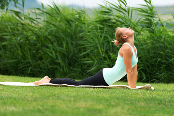 Yoga bhujangasana cobra pose by woman on green grass in the park