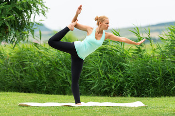 Women make yoga in nature on the green grass,Natarajasana, Lord