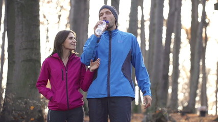 Joggers couple drinking water after run in forest