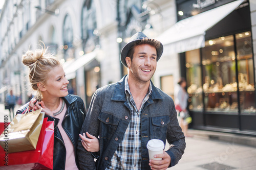 a trendy young couple walks in the city in autumn, the young wom - 73080188