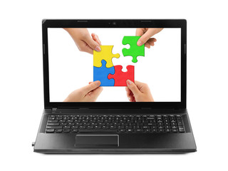 Hands and puzzle in computer notebook