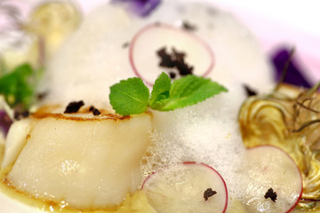 food detail of scallops with mint flavored foam, artichoke and r