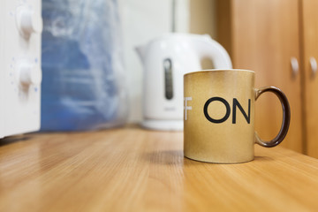 Tea mug with on letters on body standing on the table, copyspace
