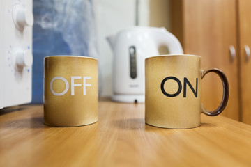 Two mugs with on off inscription standing on the table