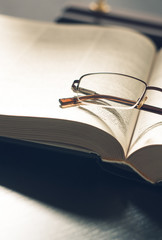 picture a pile of books and eyeglasses, with retro effect