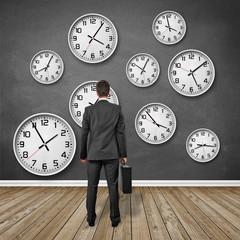 Mann steht vor Wand mit Uhren