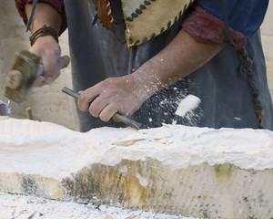 sculptor at work on a sandstone block, motion blur