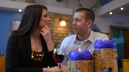 love couple sitting at a table and drink wine