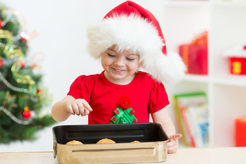 Christmas kid in Santa hat looking at cookies inside pan