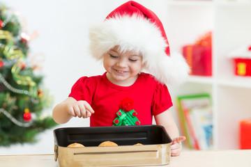 Christmas kid in Santa hat looking at cookies inside pan