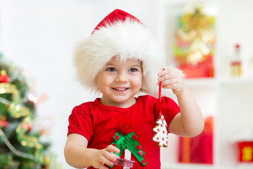 child girl in Santa hat holding Christmas biscuits