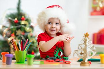 child in Santa hat making christmas tree of plasticine