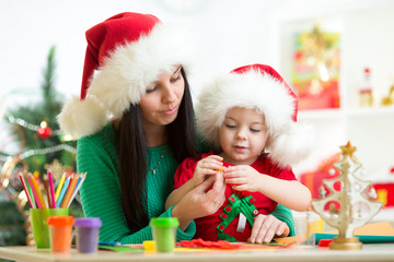 mother and kid daughter in Santa hats making christmas tree of