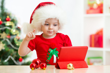 Child girl in christmas hat showing to tablet pc screen