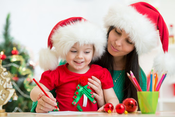 kid girl and mother writing letter to Santa
