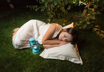 young woman in nightgown sleeping on grass at garden at night