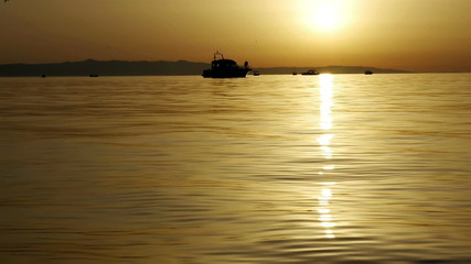 Small boats at sea in golden sunset