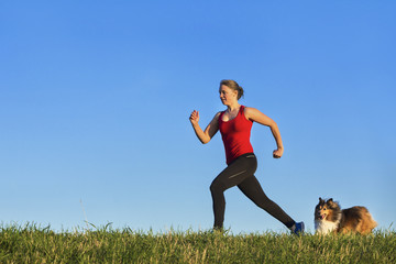 junge Fraue beim joggen mit Hund