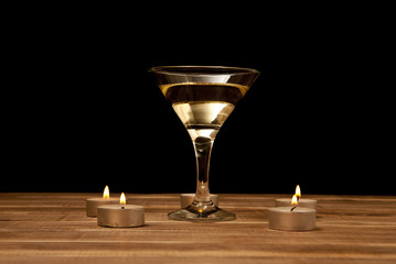 glass of martini with candles on a wooden table