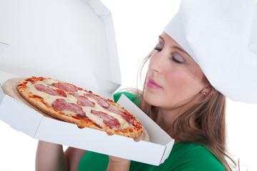 Junge sympathische Frau riecht an frischer Pizza