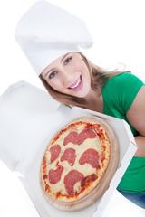 Junge sympathische Frau mit Kochmütze liefert Salami Pizza