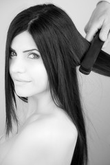 Black and white portrait of woman getting hair straightened