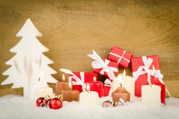 kerzen und geschenke vor holzhintergrund