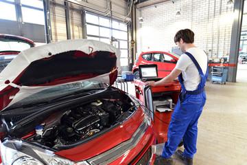 Autoechaniker mit Diagnosegerät // Mechanic auto repair