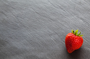 Red strawberry on slate background with copy space.