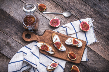 Tasty Bruschetta with jam and figs on napkin in rustic style