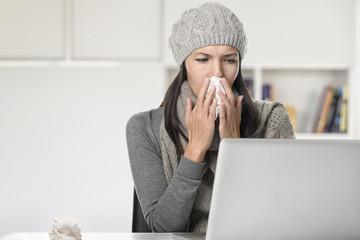 Junge Frau sitzt im Büro und putzt die Nase