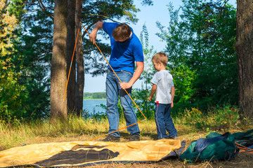 father and son set the tent on the lake