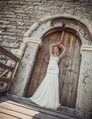 Pretty bride standing or posing on doors of castle