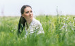 Portrait of a beautiful young woman in a grass