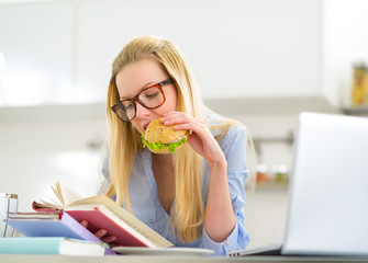 Young woman eating sandwich while studying in kitchen