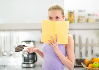 Teenager girl with chocolate reading book