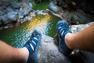 Feet in sandals on rock above lake.