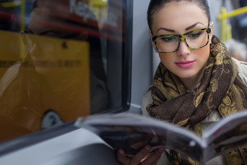 Young woman or passenger reading newspaper